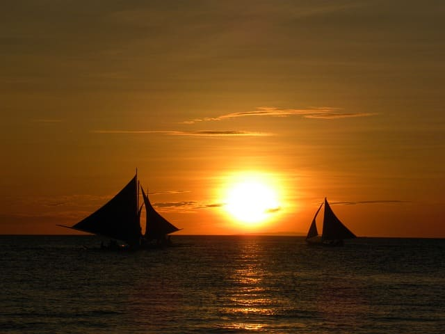 Sunset over the sea overlooking two sailboats.